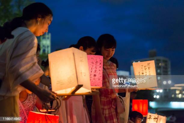 People prepare to float candle lit paper lanterns on the river during an event to commemorate the 74th anniversary of the atomic bombing of Hiroshima...