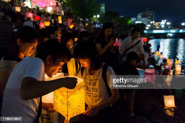 People prepare to float candle lit paper lanterns on the river to commemorate the 74th anniversary of the atomic bombing of Hiroshima at the...
