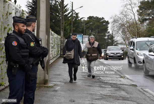 People prepare to lay flowers as gendarmes stand guard in front of the Gendarmerie Nationale in Carcassonne on March 24 2018 in tribute to the...
