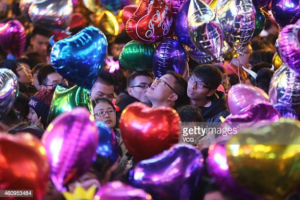 People prepare to release balloons during the New Year's Eve countdown event at Jiefangbei Pedestrian Street on December 31 2014 in Chongqing China