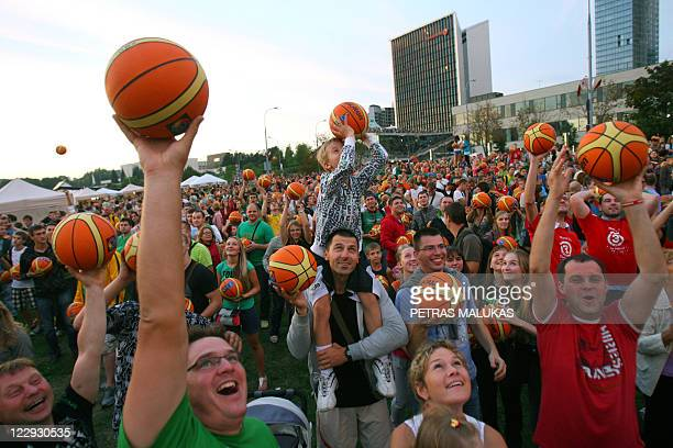 People prepare to throw basketballs in the air as they participate in an event which set the world record for basketball bouncing and which marked...