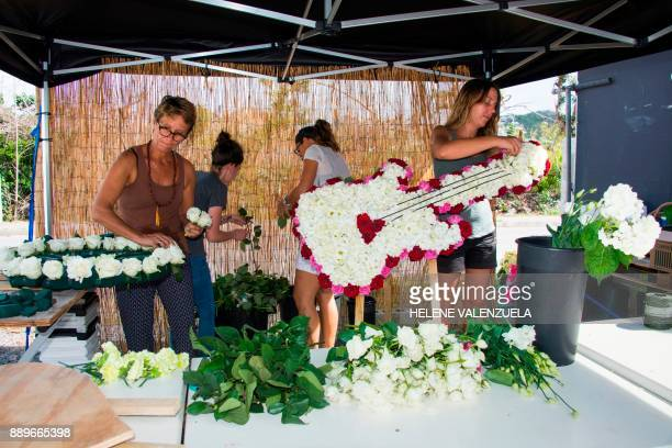 People prepare wreaths of flowers prior to a vigil for late French singer Johnny Hallyday on the French Caribbean island of SaintBarthelemy on...