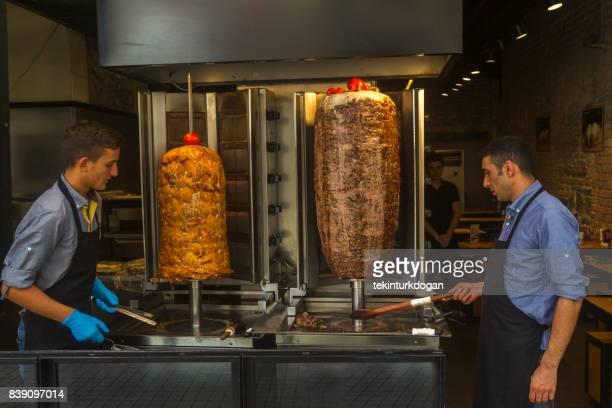 people preparing doner kebap at entrance of restaurant in istiklal street of beyoglu istanbul turkey - doner kebab stock photos and pictures