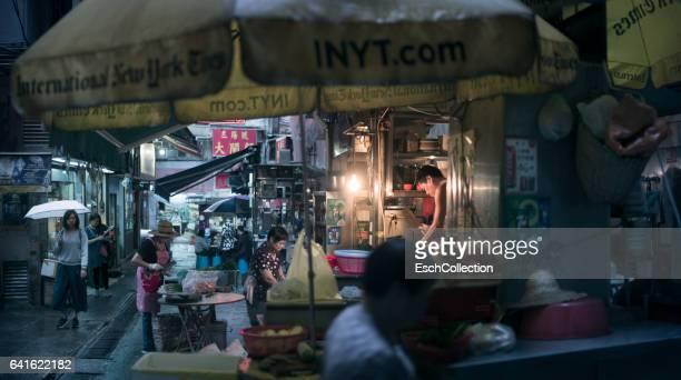 People preparing food at typical food stalls in Hong Kong