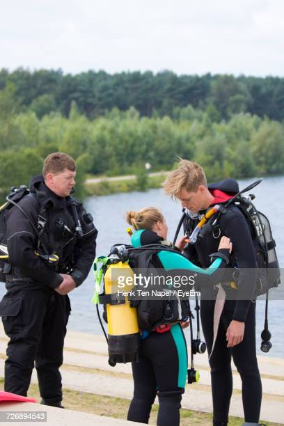 People Preparing For Scuba Diving By Lake