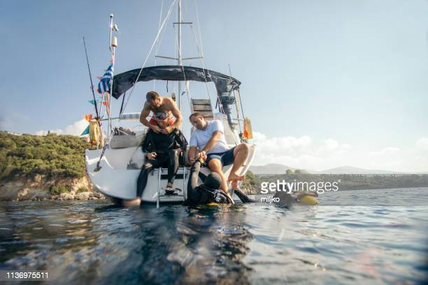 people preparing for scuba diving from sailboat - aqualung diving equipment stock pictures, royalty-free photos & images