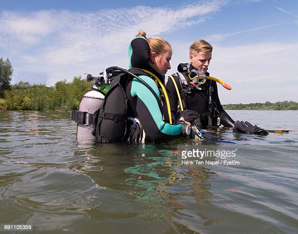 People Preparing For Scuba Diving In Lake Against Sky