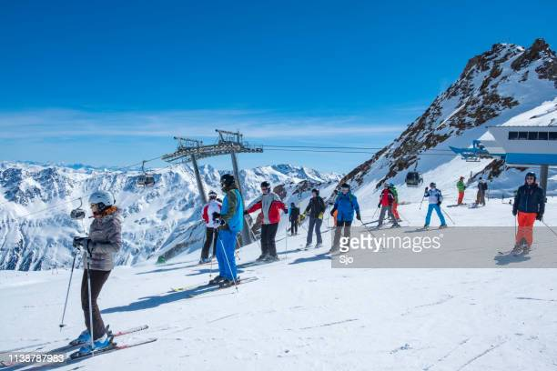 people preparing to ski and snowboard down a ski slope in the sölden ötztal ski area during a sunny winter day - solden stock pictures, royalty-free photos & images
