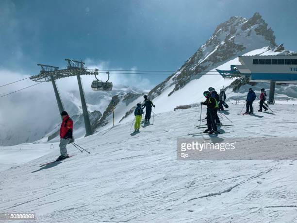 Människor som förbereder sig för att åka skidor och snowboard nedför en skidbacke i Sölden Ötztal skidområde under en solig vinter dag
