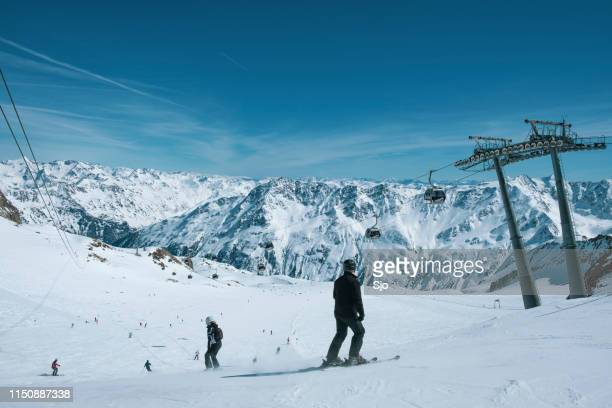 People preparing to ski and snowboard down a ski slope in the Sölden Ötztal ski area during a sunny winter day