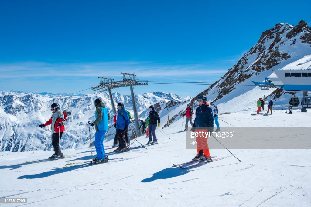 People preparing to ski and snowboard down a ski slope in the Sölden Ötztal ski area in the Austrian Alps during a sunny winter day. : Stock Photo