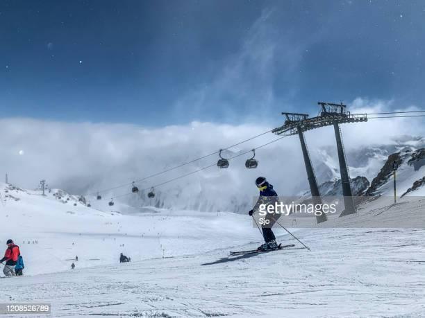 """mensen die zich voorbereiden om te skiën en snowboarden op een skipiste in het skigebied sölden ötztal tijdens een zonnige winterdag - """"sjoerd van der wal"""" or """"sjo"""" stockfoto's en -beelden"""