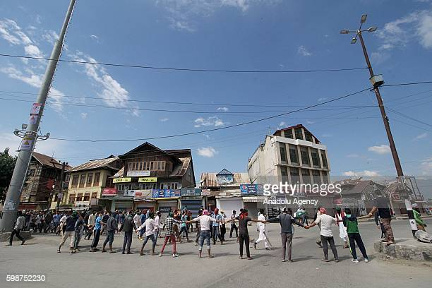 People prevent confrontation between police and protesters by blocking the road during the funeral ceremony of 12 years oldDanishSultanin Srinagar...