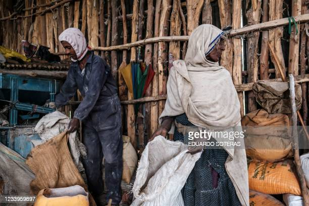 People process sorghum in a mill, in a rural area near the village of Dabat, 70 kilometres northeast from the city of Gondar, Ethiopia, on July 13,...