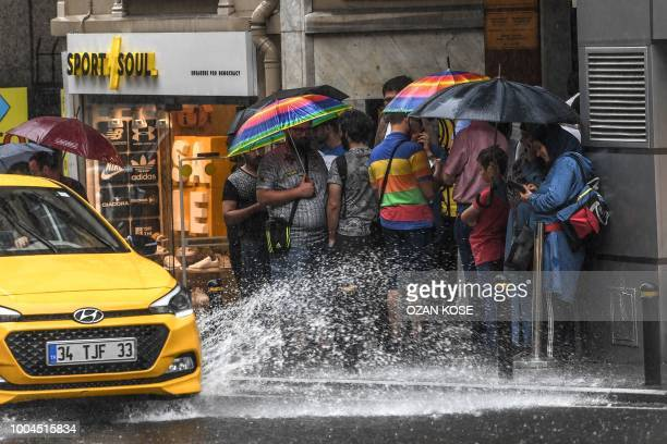 People protect themself from the rain with umbrellas on July 24 2018 at Karakoy district in Istanbul