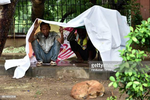 People protect themselves from rains with a plastic sheet on September 22 2017 in New Delhi India DelhiNCR got some respite from the heat and...