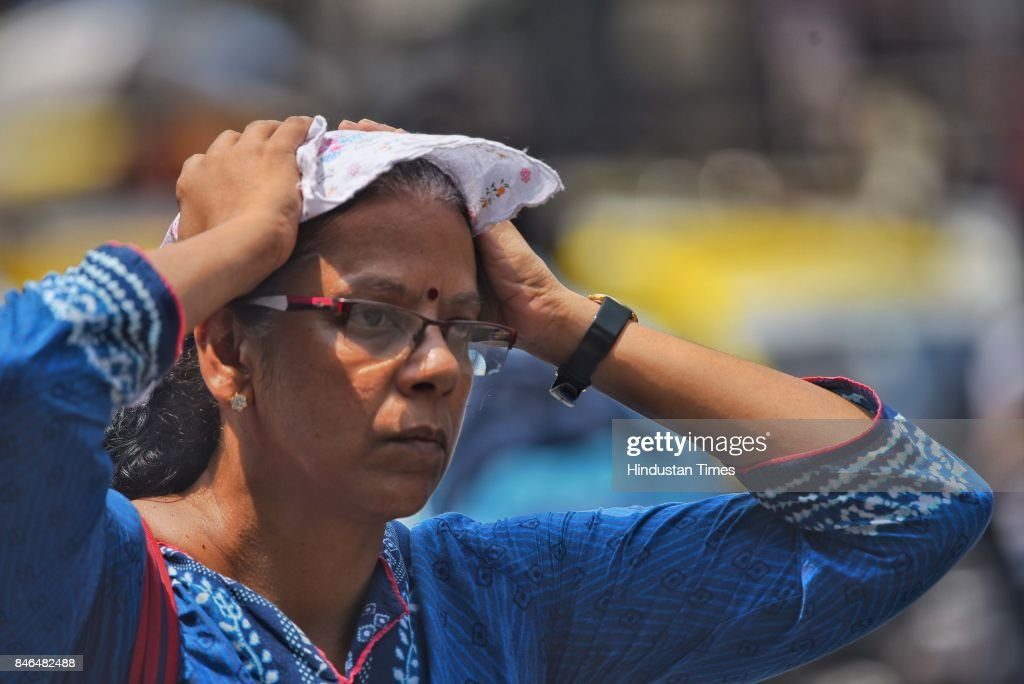 People protect themselves from the heat at Dadar, on September 11, 2017 in Mumbai, India. Hot weather had taken over Mumbai for the last few days. On Monday, city had recorded a maximum temperature of 35.5 degree Celsius while the maximum temperature recorded was 33.4 degree Celsius.