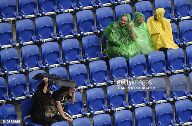 People protect themselves from the rain during the Euro 2016 group C football match between Ukraine and Northern Ireland at the Parc Olympique...