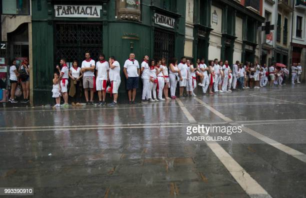 People protect themselves from the rain on the first day of the San Fermin bull run festival in Pamplona northern Spain on July 7 2018 Each day at...