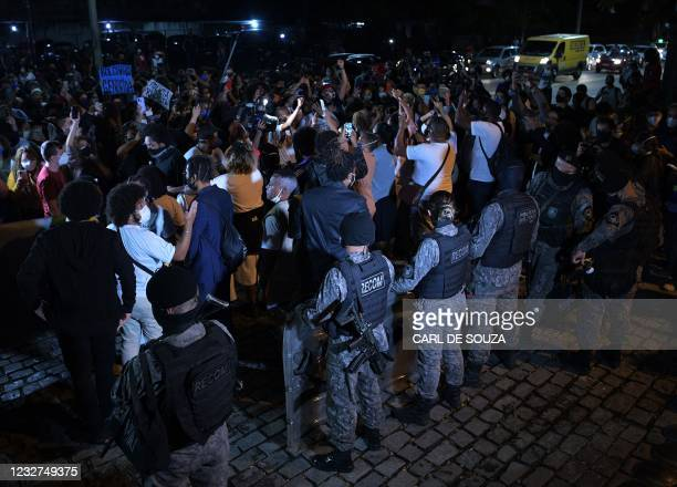 People protest against a police operation to combat alleged drug traffickers that killed 25 people Thursday as police stand guard at the Jacarezinho...