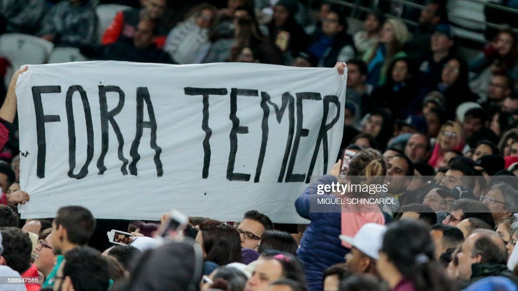 TOPSHOT - People protest against Brazil's interim president Michel Temer during the Rio 2016 Olympic Games women's football quarterfinal match between Canada and France at the Corinthians Arena in Sao Paulo, Brazil, on August 12, 2016. / AFP PHOTO / Miguel SCHINCARIOL