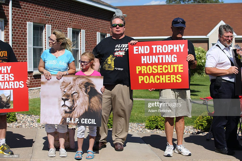 People protest against poaching after the death of Cecil the lion, in the parking lot of Dr. Walter Palmer's River Bluff Dental Clinic on July 29, 2015 in Bloomington, Minnesota. According to reports, the 13-year-old lion was lured out of a national park in Zimbabwe and killed by Dr. Palmer, who had paid at least $50,000 for the hunt.