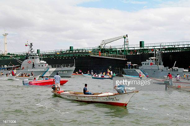 People protest against the presence of Venezuelan Coast Guard vessels patrolling near the oil tanker Pilin Leon after troops took control of the...