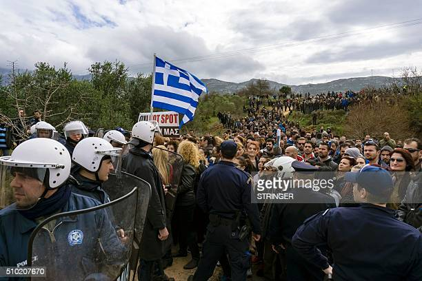 People protest against the socalled 'hotspot' being built for refugees and migrants on the Aegean island of Kos on February 14 2015 Greek riot police...