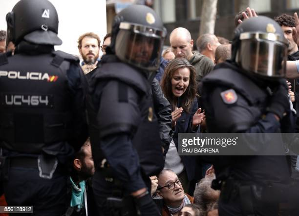 People protest and sit in front of Spanish police officers after the seizing ballotboxes in a polling station in Barcelona on October 1 on the day of...