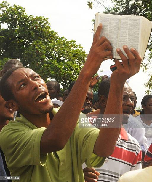 People protest as a man points to his bible on July 19 2013 in PortauPrince urging lawmakers not to pass legislation that would legalize samesex...