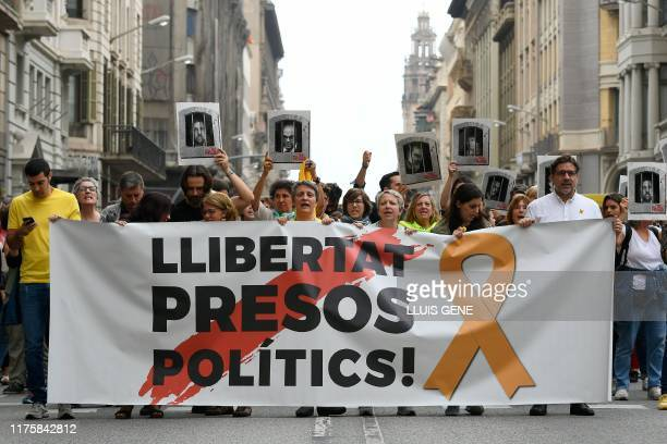 """People protest holding a banner reading """"Free political prisoners"""" in Barcelona on October 14 after Spain's Supreme Court sentenced nine Catalan..."""