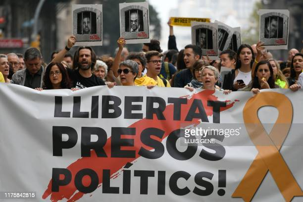 "People protest holding a banner reading ""Free political prisoners"" in Barcelona on October 14 after Spain's Supreme Court sentenced nine Catalan..."