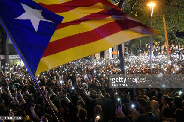 TOPSHOT People protest holding their mobile phones and a Catalan proindependence Estelada flag in Barcelona on October 15 as Catalonia geared up for...