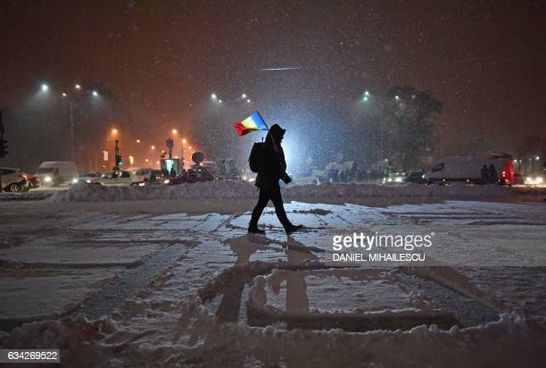 People protest in front of the government headquarters in Bucharest, during a protest against controversial corruption decrees on February 8, 2017. -...