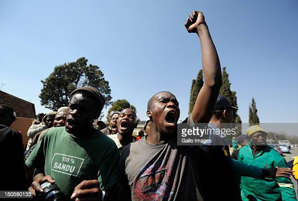 People protest outside the courtroom as Chris Mahlangu and his coaccused Patrick Ndlovu appear in court for sentencing in connection with the murder...