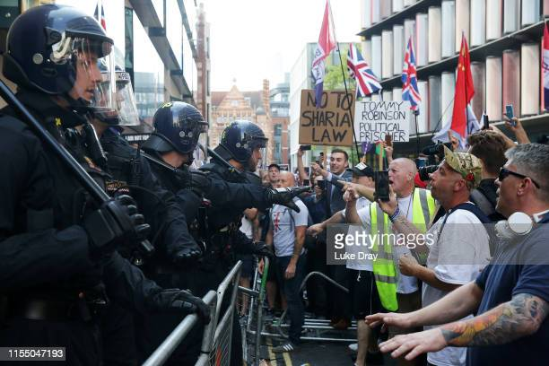 People protest outside the Old Bailey after British farright activist and former leader and founder of English Defence League Tommy Robinson whose...