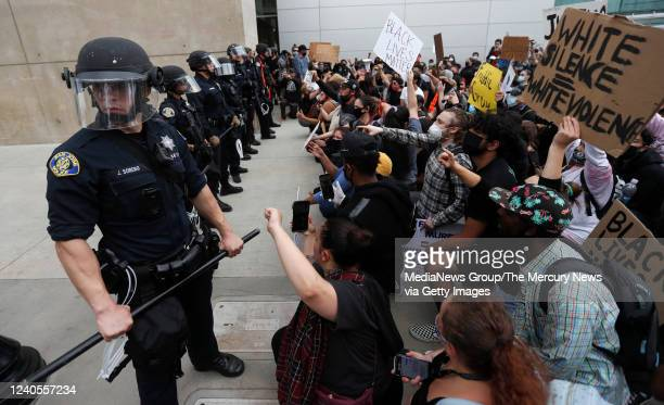 People protest the killing of George Floyd in front of San Jose Police officers outside of San Jose City Hall in downtown San Jose Calif on Sunday...