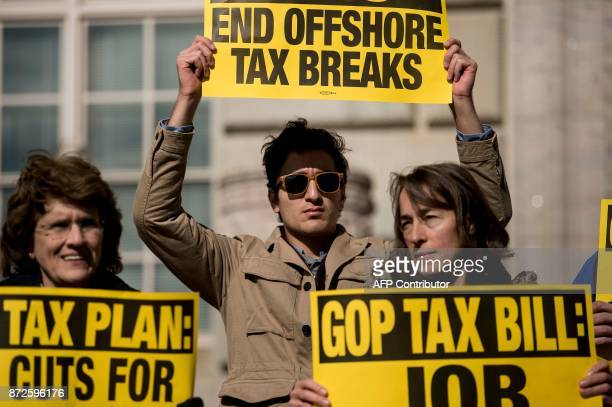 People protest the Republican tax reform plan outside the Department of Commerce on November 10, 2017 in Washington, DC. / AFP PHOTO / Brendan...
