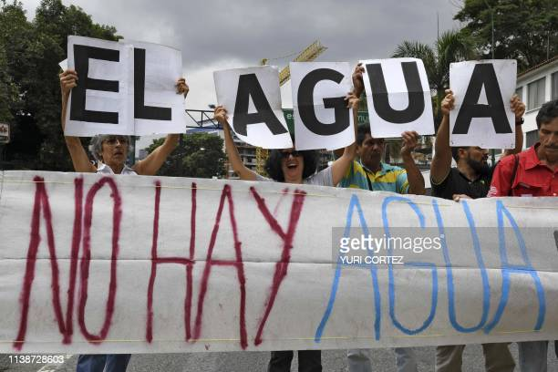 People protest water shortage with a banner reading 'There is no water' during the Earth Day at Las Mercedes neighborhood in Caracas on April 22 2019