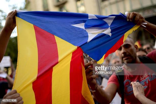 People protesting against the Catalan region's independence bid cut a catalan independentist flag in front the nationalist electoral alliance CiU...