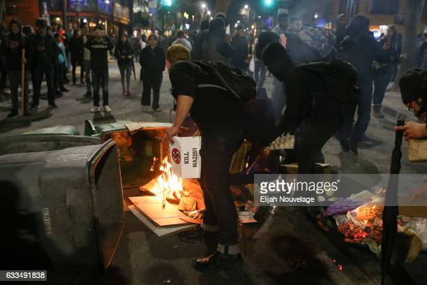 People protesting controversial Breitbart writer Milo Yiannopoulos burn trash and cardboard in the street on February 1 2017 in Berkeley California A...