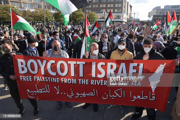 """People protesting for the rights of Palestinians and against the Israeli military bombardments of Gaza hold a banner that reads: """"Boycott Israel"""" as..."""