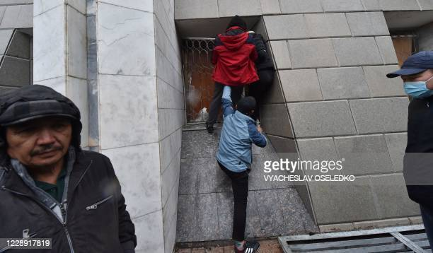 People protesting the results of a parliamentary vote are seen outside the seized main government building, known as the White House, in Bishkek on...