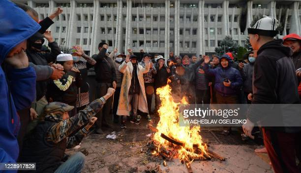 TOPSHOT People protesting the results of a parliamentary vote gather by a bonfire in front of the seized main government building known as the White...