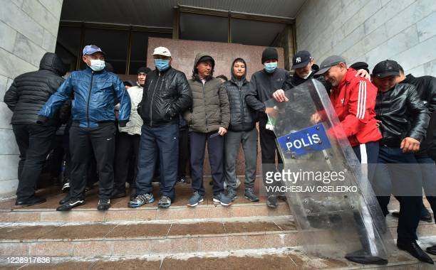 People protesting the results of a parliamentary vote gather outside the seized main government building, known as the White House, in Bishkek, on...