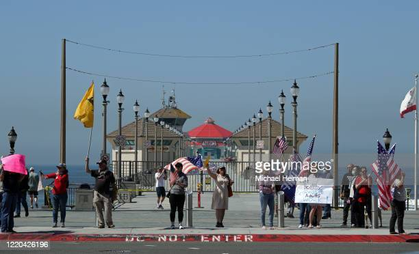 People protesting the statewide stay at home order stand in front of the Huntington Beach pier on April 22 2020 in Huntington Beach California...