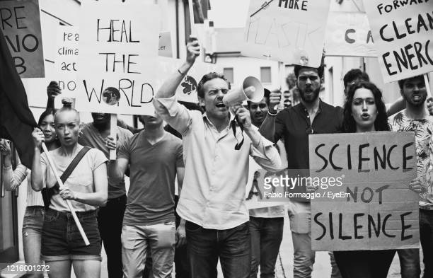 people protesting while standing on land - protestor stock pictures, royalty-free photos & images
