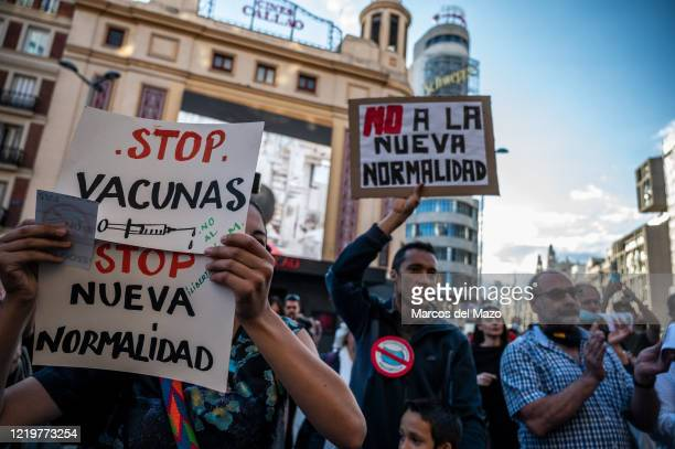 People protesting with placards against new normality and New World Order conspiracy theory. Placards reads: stop vaccines, no to the new normality.
