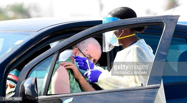 People pull up in their vehicles for Covid-19 vaccines in the parking lot of The Forum in Inglewood, California on January 19, 2021. - Five...