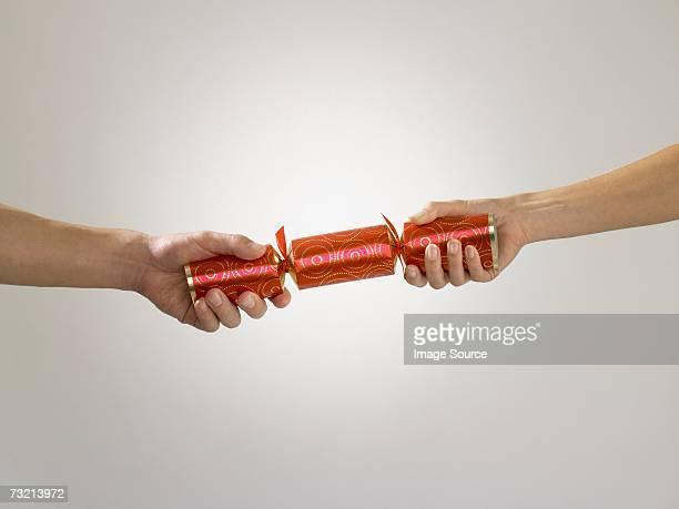 people pulling cracker - クリスマスクラッカー ストックフォトと画像